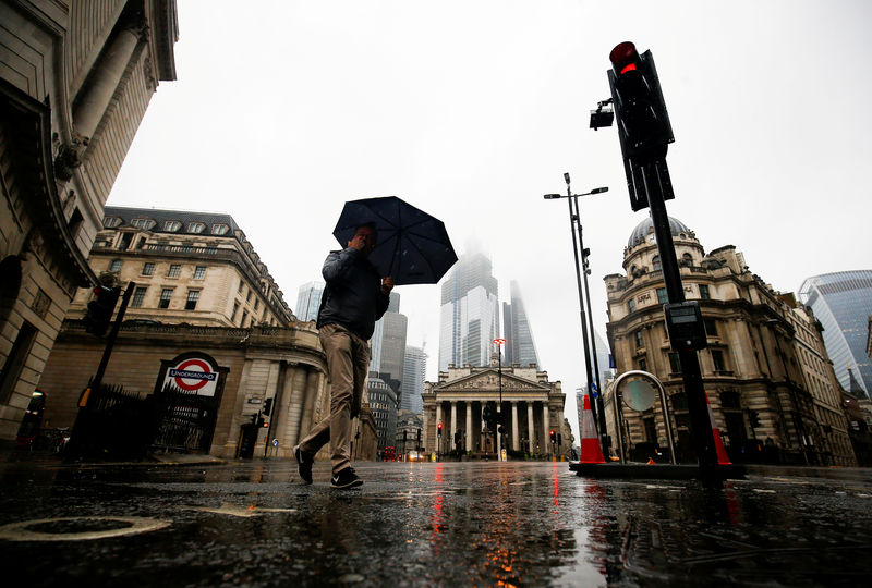 © Reuters. FILE PHOTO: People walk through the financial district during rainy weather in London