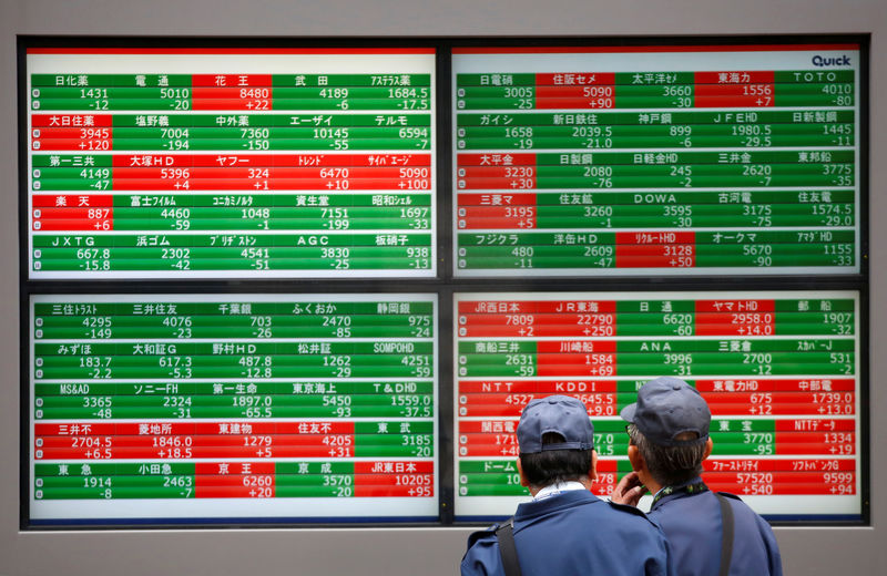 © Reuters. Men look at stock quotation boards outside a brokerage in Tokyo