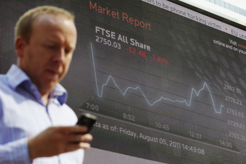 © Reuters. FILE PHOTO:  A man passes a screen showing the activity of the FTSE index at Canary Wharf financial district in London