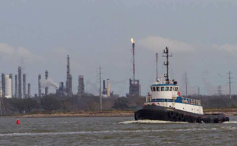 © Reuters. FILE PHOTO: A tug boat navigates the Houston ship channel with a flare from an oil refinery and storage facility in the background south of downtown Houston