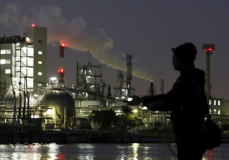 © Reuters. FILE PHOTO - Smoke is emitted from a chimney as a man fishes at the Keihin industrial zone in Kawasaki