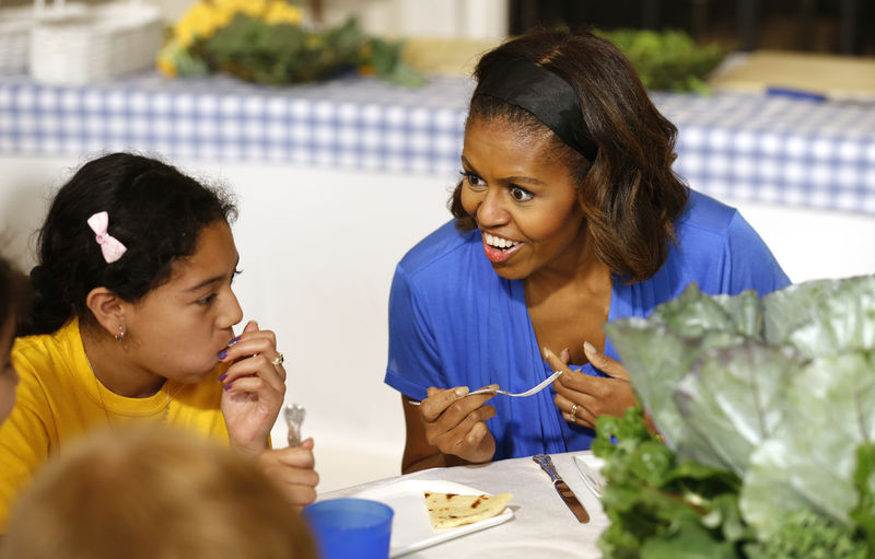 © Reuters. U.S. first lady Obama speaks with school children after making a salad together using the summer crop from the White House Kitchen Garden at the White House in Washington