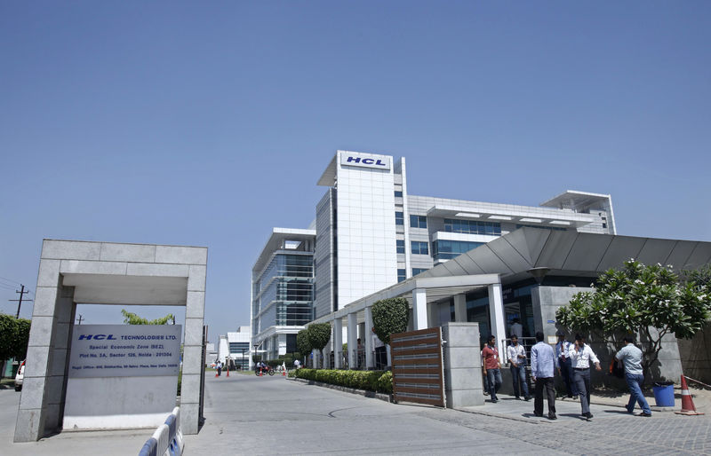 © Reuters. People walk in front of the HCL Technologies Ltd office at Noida
