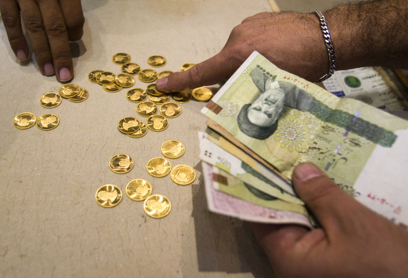 © Reuters. A customer buys Iranian gold coins at a currency exchange office in Tehran