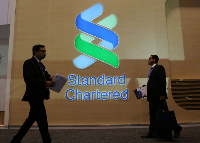 © Reuters. People pass by the logo of Standard Chartered plc at the SIBOS banking and financial conference in Toronto
