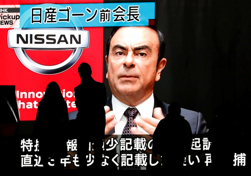 © Reuters. Passersby are silhouetted as a huge street monitor broadcasts news reporting ousted Nissan Motor chairman Carlos Ghosn's indictment and re-arrest in Tokyo