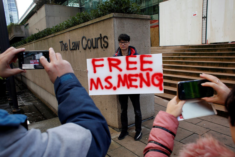 © Reuters. A man holds a sign outside of the B.C. Supreme Court bail hearing of Huawei CFO Meng Wanzhou, who is being held on an extradition warrant in Vancouver
