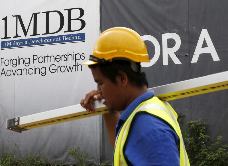© Reuters. FILE PHOTO:  A construction worker walks past a 1Malaysia Development Berhad (1MDB) billboard at the Tun Razak Exchange development in Kuala Lumpur, Malaysia