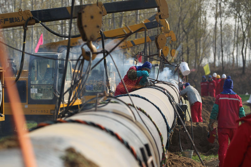 © Reuters. Workers lay pipelines for China National Petroleum Corp (CNPC)'s Shaanxi-Beijing natural gas pipeline network in Hebei