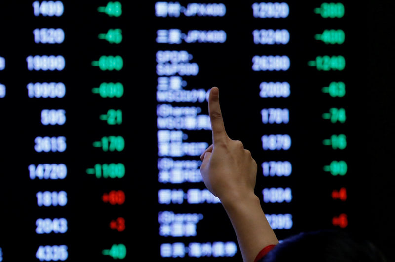 © Reuters. FILE PHOTO:  A woman points to an electronic board showing stock prices as she poses in front of the board after the New Year opening ceremony at the Tokyo Stock Exchange (TSE), held to wish for the success of Japan's stock market, in Tokyo