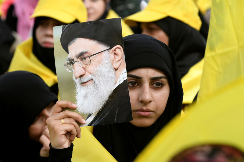© Reuters. FILE PHOTO: A woman carries a picture of Iran's Supreme Leade Khamenei as she watches Lebanon's Hezbollah leader Nasrallah appear on a screen during a live broadcast to speak to his supporters at an event marking Resistance and Liberation Day in