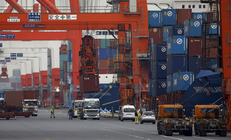 © Reuters. Workers load containers onto trucks from a cargo ship at a port in Tokyo