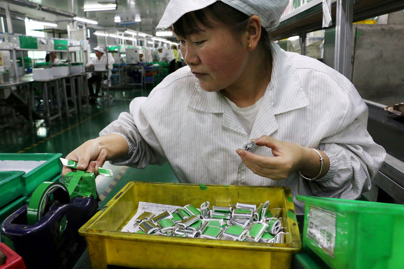 © Reuters. FILE PHOTO: Employee works at a production line of lithium ion batteries inside a factory in Dongguan