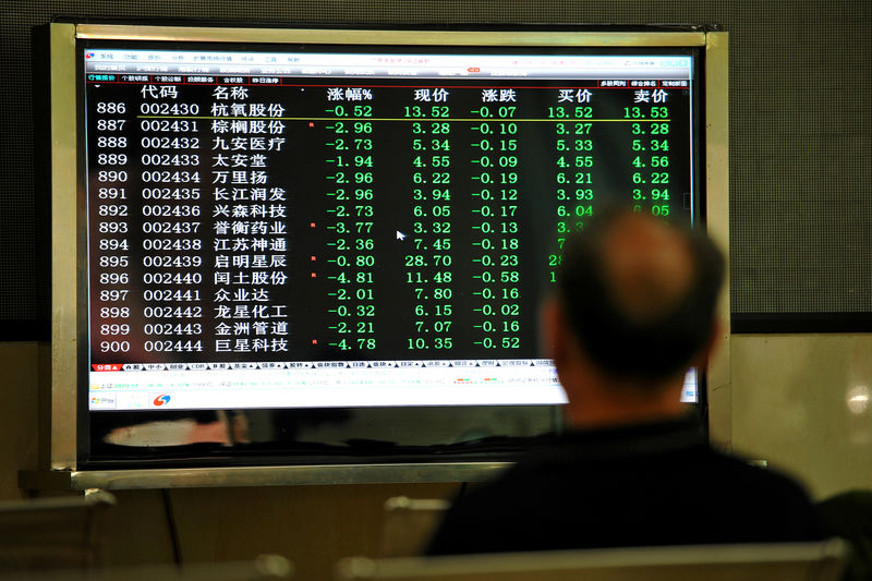 © Reuters. FILE PHOTO: Man sits in front of a screen displaying stock information at a brokerage house in Jinhua
