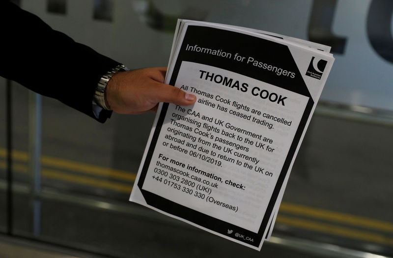 © Reuters. A man holds information on Thomas Cook flights at Manchester Airport