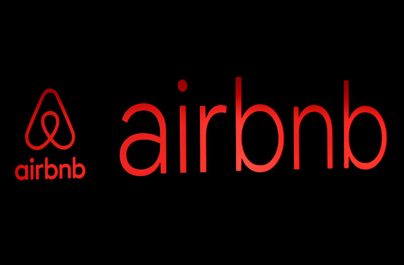 © Reuters. FILE PHOTO: The logos of Airbnb are displayed at an Airbnb event in Tokyo