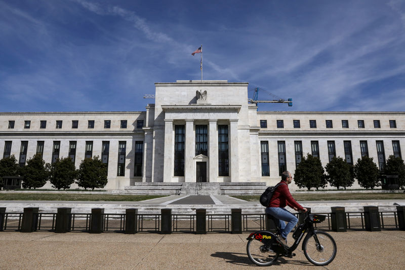 © Reuters. FILE PHOTO: A man rides a bike in front of the Federal Reserve Board building on Constitution Avenue in Washington