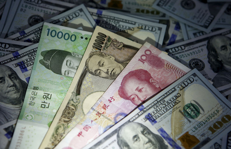 © Reuters. South Korean won, Chinese yuan and Japanese yen notes are seen on U.S. 100 dollar notes in this picture illustration taken in Seoul
