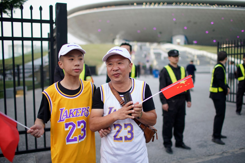 © Reuters. Fans in LeBron James jerseys hold Chinese flags outside the Mercedes-Benz Arena before the NBA exhibition game between Brooklyn Nets and Los Angeles Lakers in Shanghai