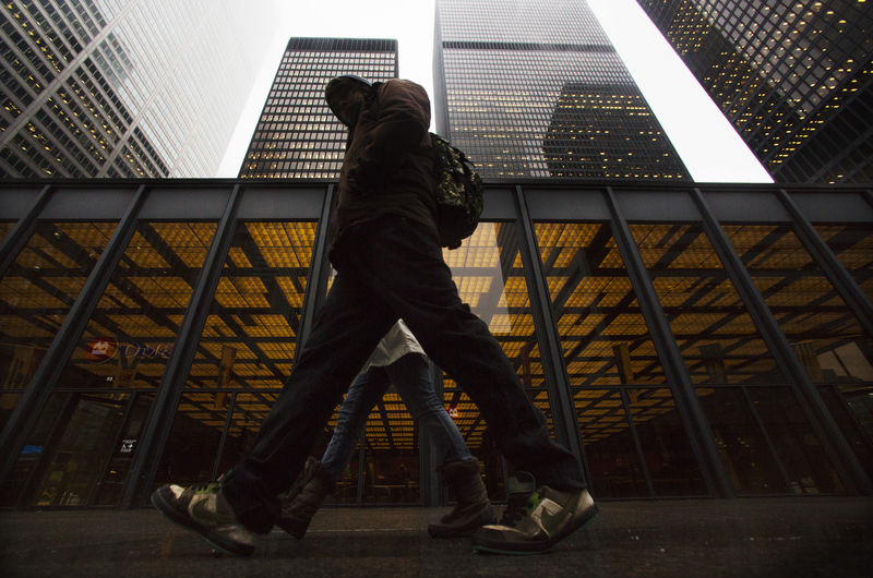 © Reuters. A man walks in front of buildings in the financial district in Toronto