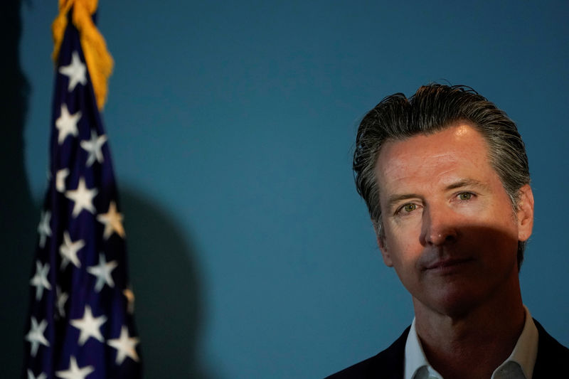 © Reuters. FILE PHOTO: California governor Gavin Newsom stands next to an American flag as he waits to speak at a news conference in San Diego