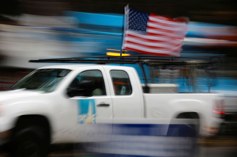 © Reuters. A PG&E truck carrying an American Flag drives past PG&E repair trucks in Paradise