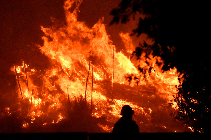 Deadly Los Angeles wildfire burns with subdued fury after change in we