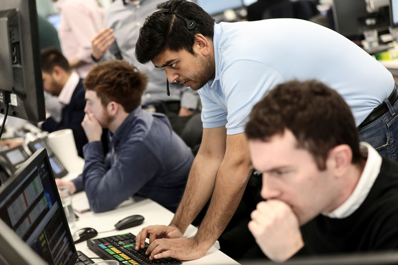 © Reuters. Traders looks at financial information on computer screens on the IG Index trading floor