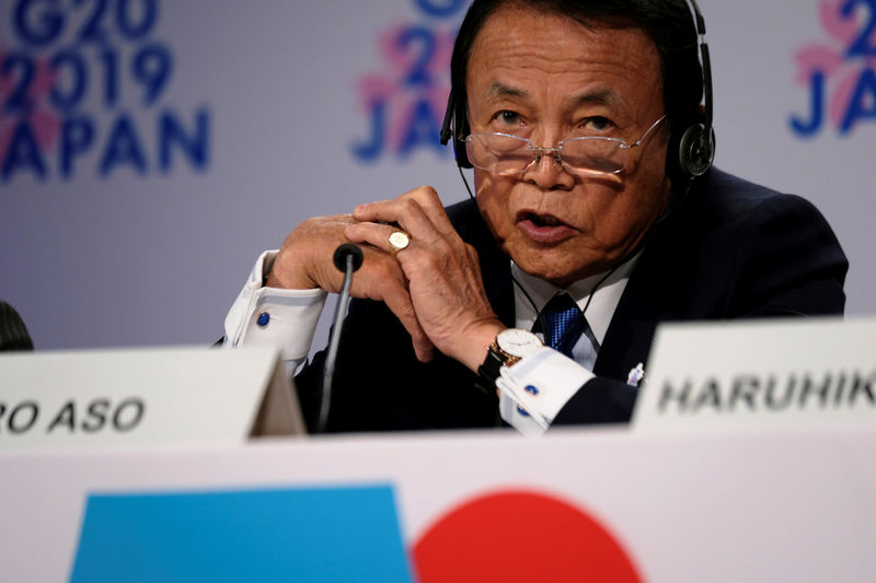 Japan's Aso says risks tilted to downside but encouraged by U.S.-China