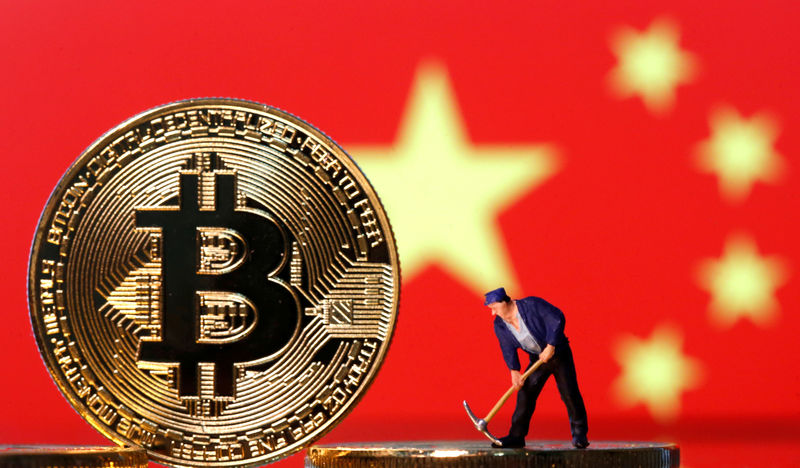 © Reuters. FILE PHOTO: Picture illustration of a small toy figurine and representations of the Bitcoin virtual currency displayed in front of an image of China's flag