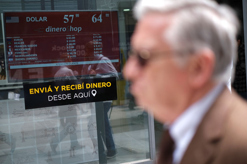 © Reuters. People walk past a screen showing currency exchange rates at a currency exchange shop in Buenos Aires