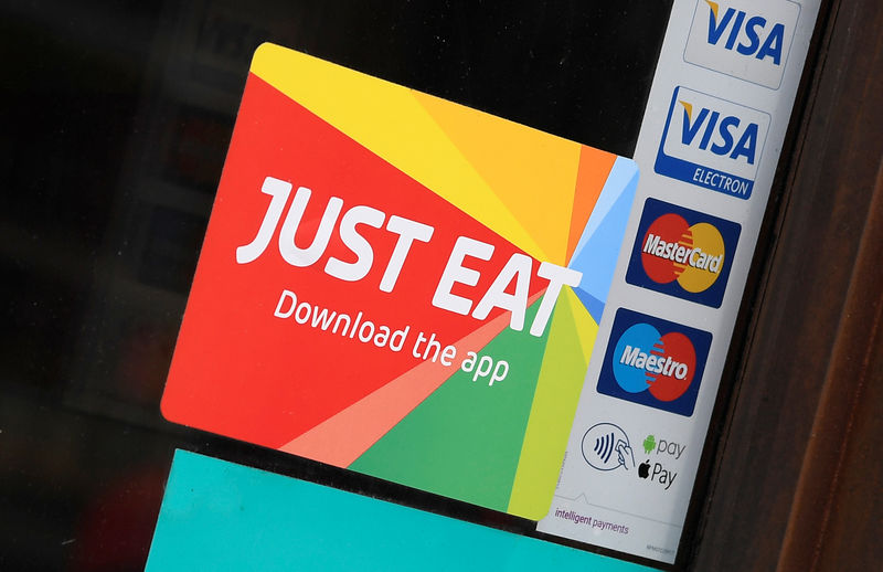 © Reuters. Signage for Just Eat is seen on the window of a restaurant in London