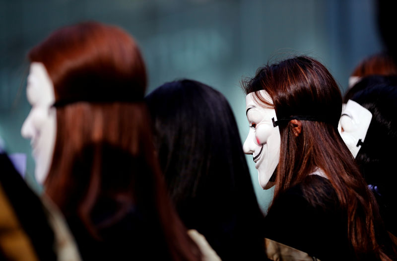 © Reuters. University students wearing Guy Fawkes masks pose for a photoshot to support anti-government protests before their graduation ceremony at the Hong Kong Polytechnic University in Hong Kong