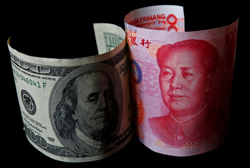 © Reuters. FILE PHOTO: A 100 yuan banknote is placed next to a $100 banknote in this picture illustration taken in Beijing