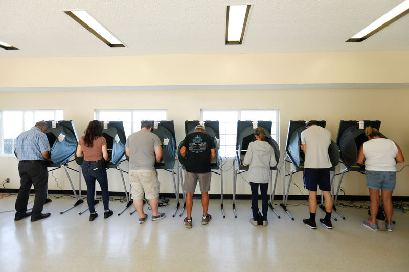 © Reuters. People vote at electronic polling stations in Huntington Beach, California