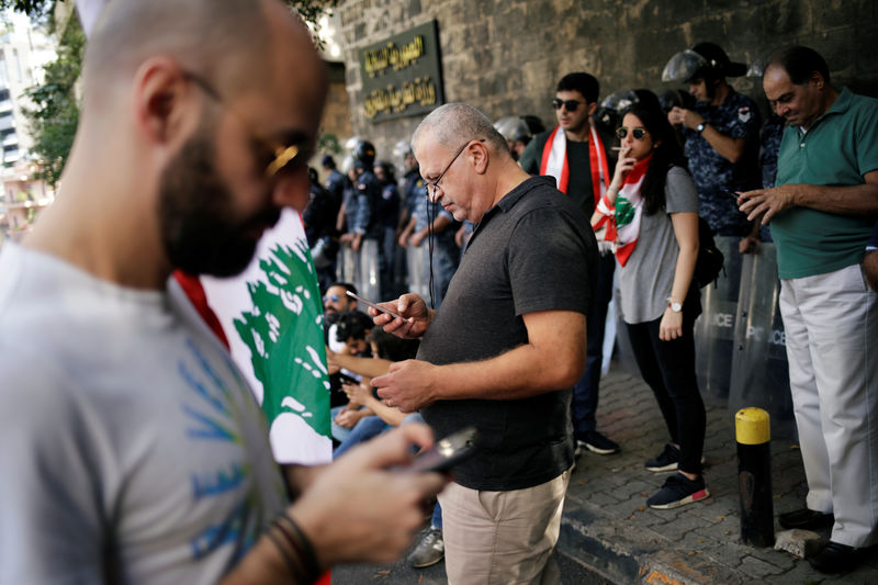 © Reuters. Protesters use their cellphones as they stand in front of police officers outside of the Ministry of Foreign Affairs and Emigrants during a protest in Beirut