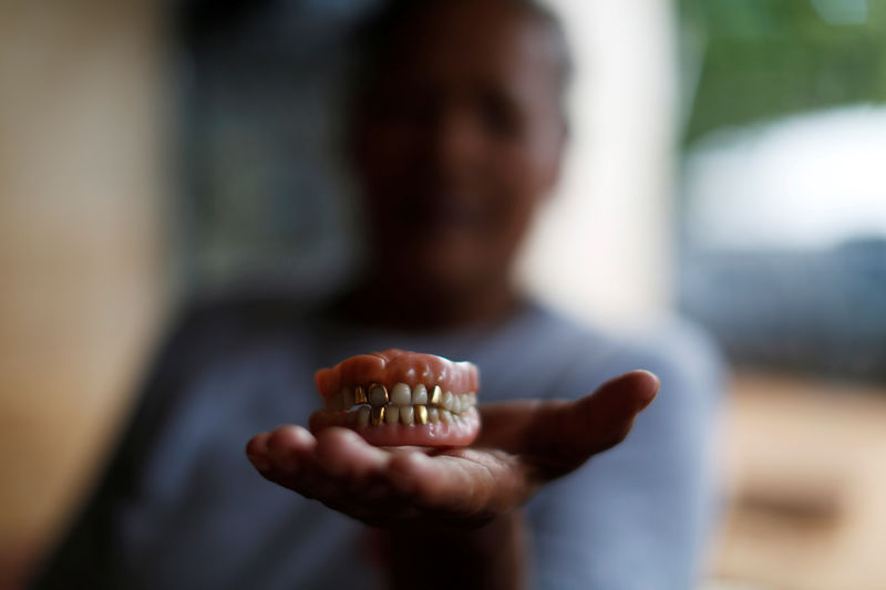 © Reuters. Miriam Marquez shows a dental prosthesis of her mother in law killed by Salvadorean soldiers in the village of El Mozote