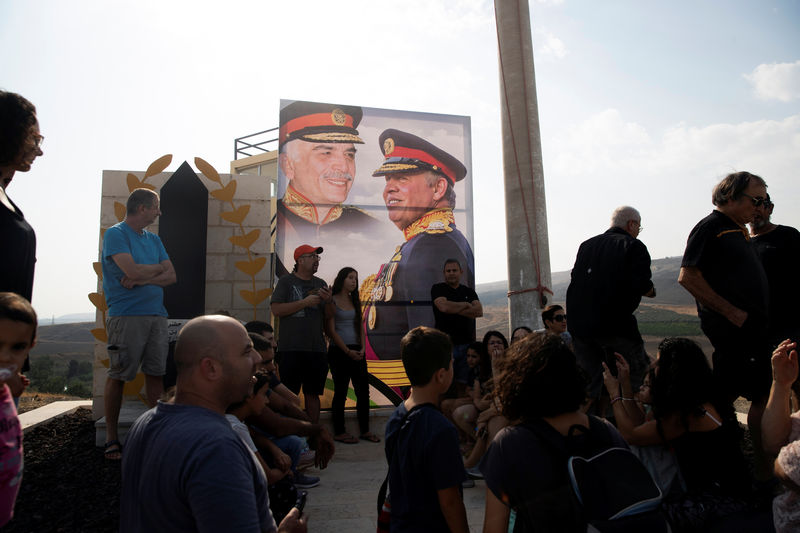 © Reuters. A picture of Jordanian King Abdullah and his father, the late King Hussein, is seen as people visit the