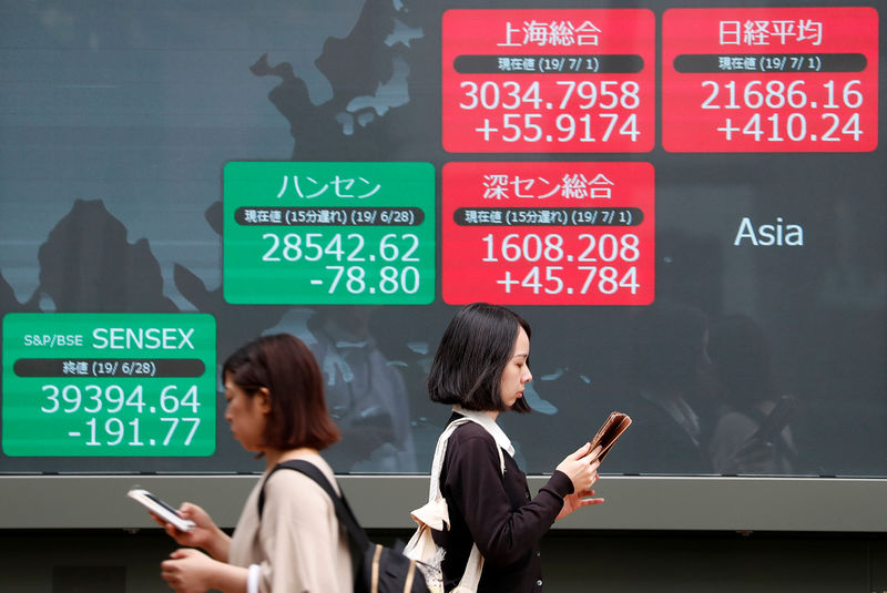 © Reuters. Passerbys walk past an electric screen showing Asian markets indices outside a brokerage in Tokyo