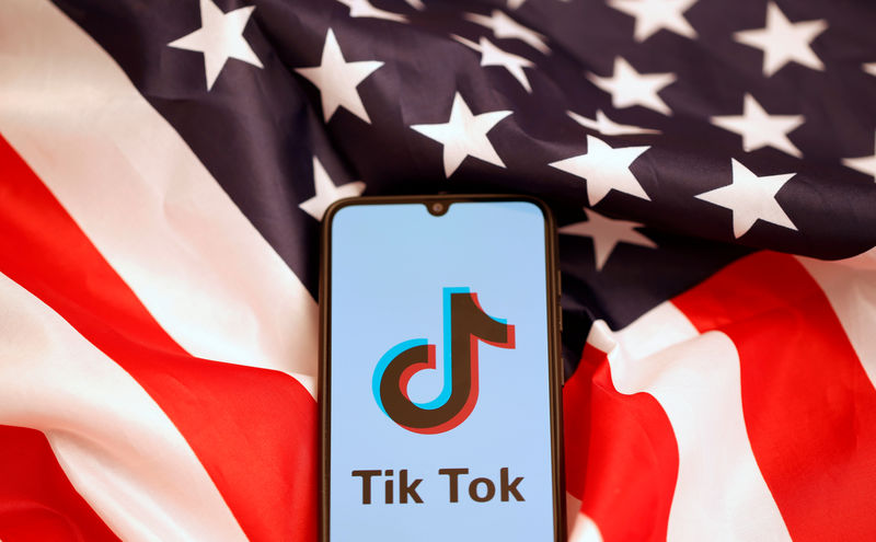 © Reuters. Tik Tok logo is displayed on the smartphone while standing on the U.S. flag in this illustration