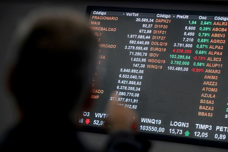 © Reuters. FILE PHOTO: Currency exchange rates of euro and the U.S. dollar are seen on an electronic board as a man points at it on the floor of Brazil's B3 Stock Exchange in Sao Paulo
