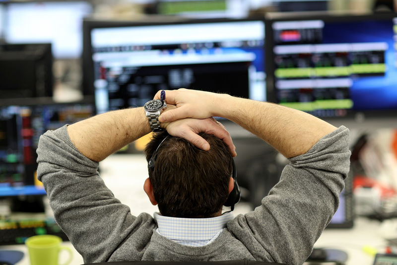 © Reuters. FILE PHOTO: A broker looks at financial information on computer screens on the IG Index trading floor