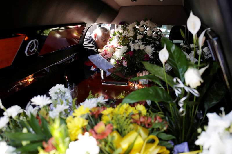 © Reuters. A man puts flowers inside a hearse of one of the victims of a mass shooting at a Walmart store during a tribute in El Paso