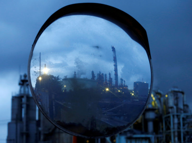 © Reuters. FILE PHOTO: Chimneys of a factory are reflected in a traffic mirror at the Keihin industrial zone in Kawasaki, south of Tokyo