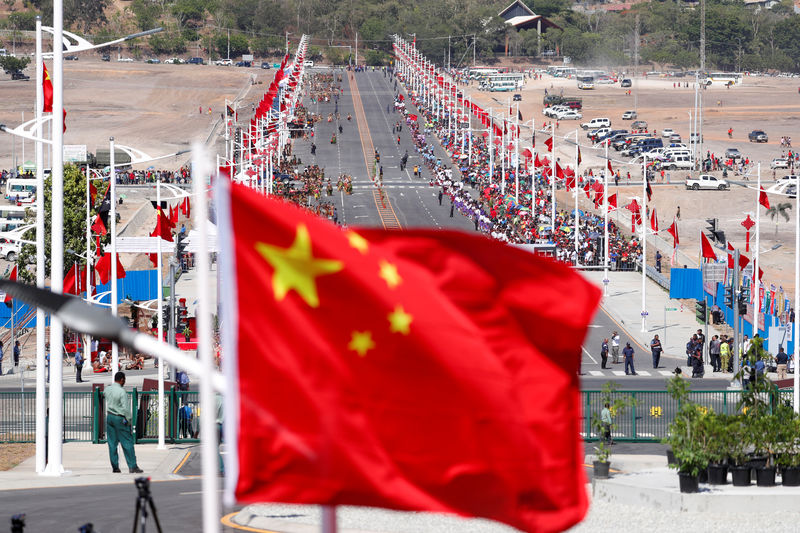 © Reuters. FILE PHOTO:  A Chinese national flag flies in front of a Chinese-built main road, before a welcome ceremony for China's President Xi Jinping ahead of the APEC Summit in Port Moresby
