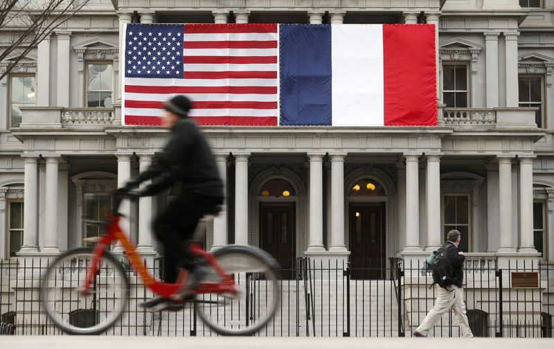 © Reuters. U.S. and French flags fly next to the White House to honor French President Hollande in Washington
