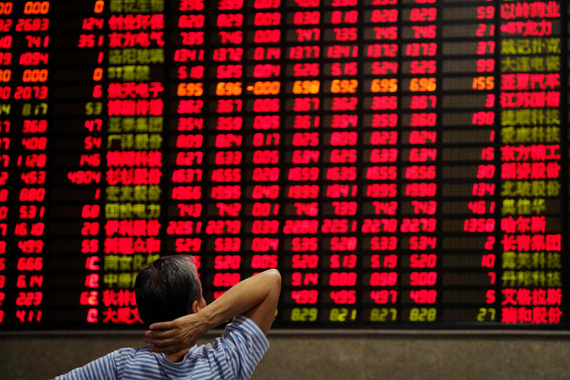 © Reuters. An investor looks at an electronic board showing stock information at a brokerage house in Shanghai