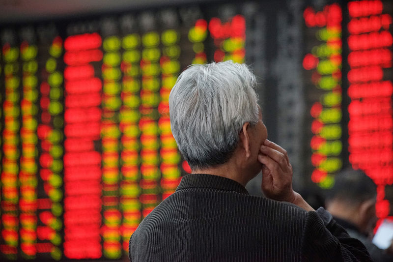 © Reuters. An investor looks at an electronic board showing stock information at a brokerage house in Nanjing