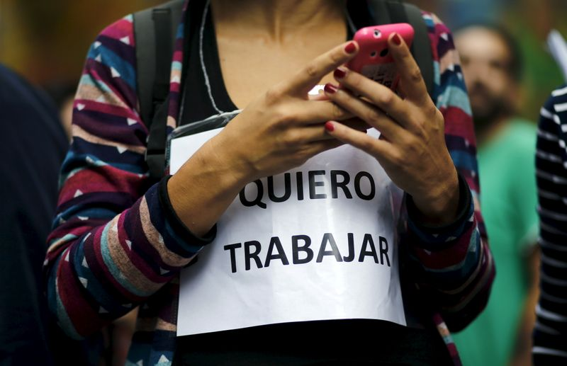 © Reuters. FILE PHOTO: A state worker looks at her phone while wearing a sign outside the Labour Ministry, during a protest against layoffs, in Buenos Aires