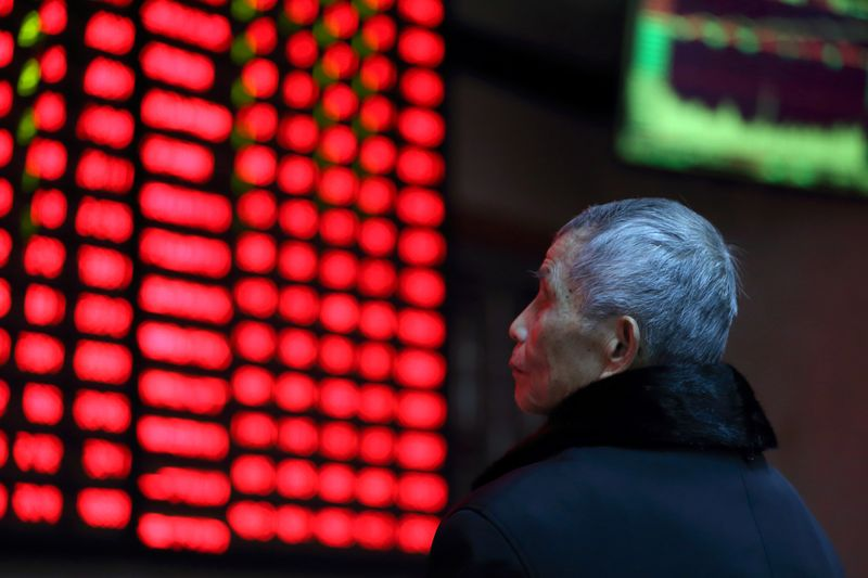 © Reuters. FILE PHOTO: A man looks on in front of an electronic board showing stock information at a brokerage house in Nanjing
